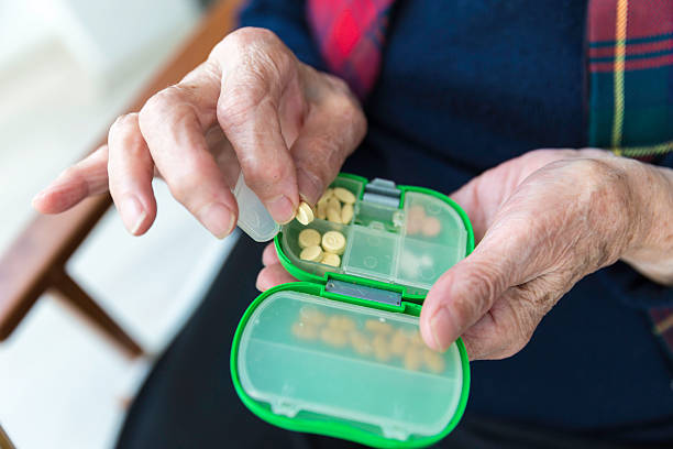 Elderly Turkish woman taking pills from medicine box stock photo
