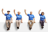 istock Elderly volunteers sitting on panel and waving 1172487139