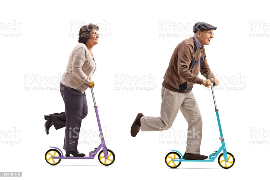 Elderly woman and an elderly man riding scooters stock photo