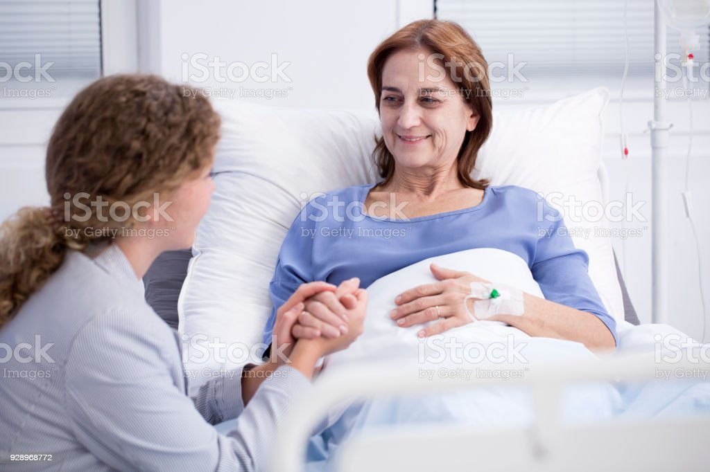 Elderly woman and caring daughter stock photo