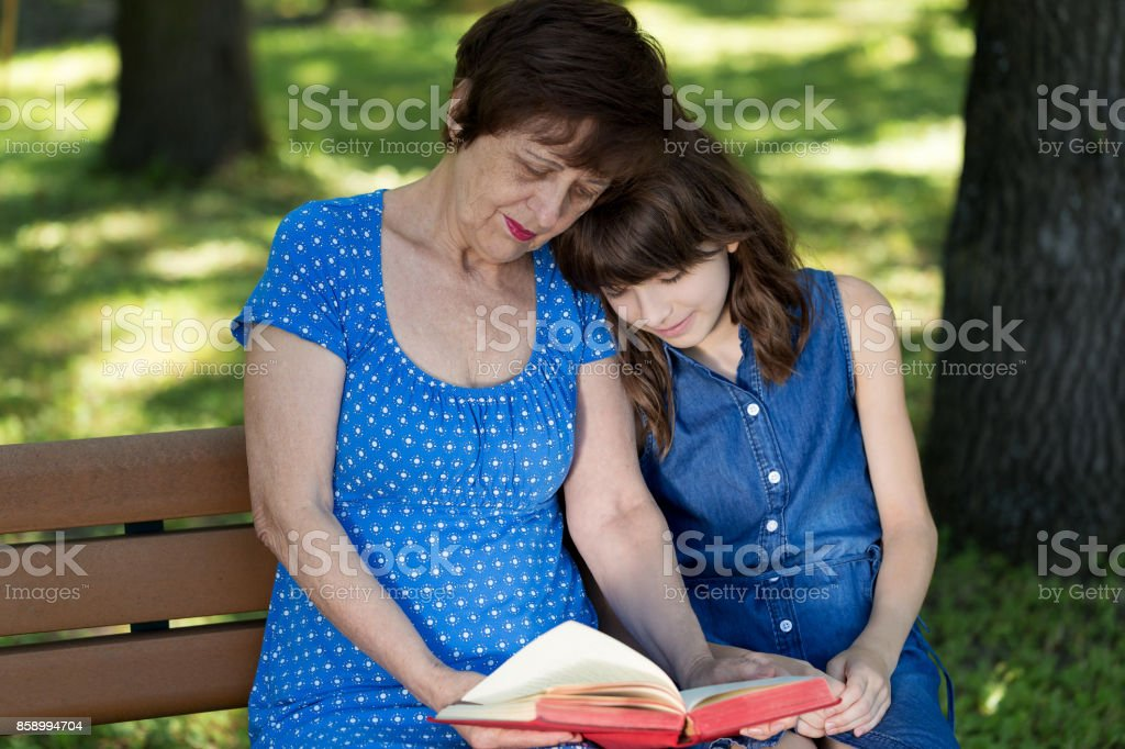 Elderly woman and girl are sitting on the bench and reading a book against green nature background. Grandmother and granddaughter. stock photo