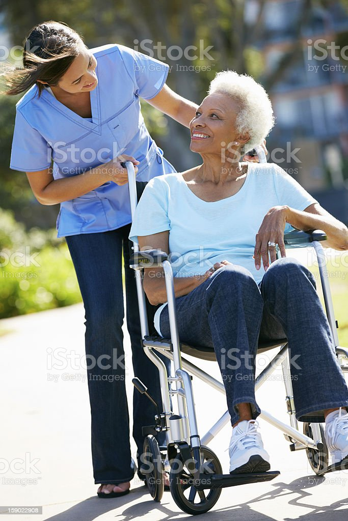 Elderly woman and her nurse going for a walk in fresh air stock photo