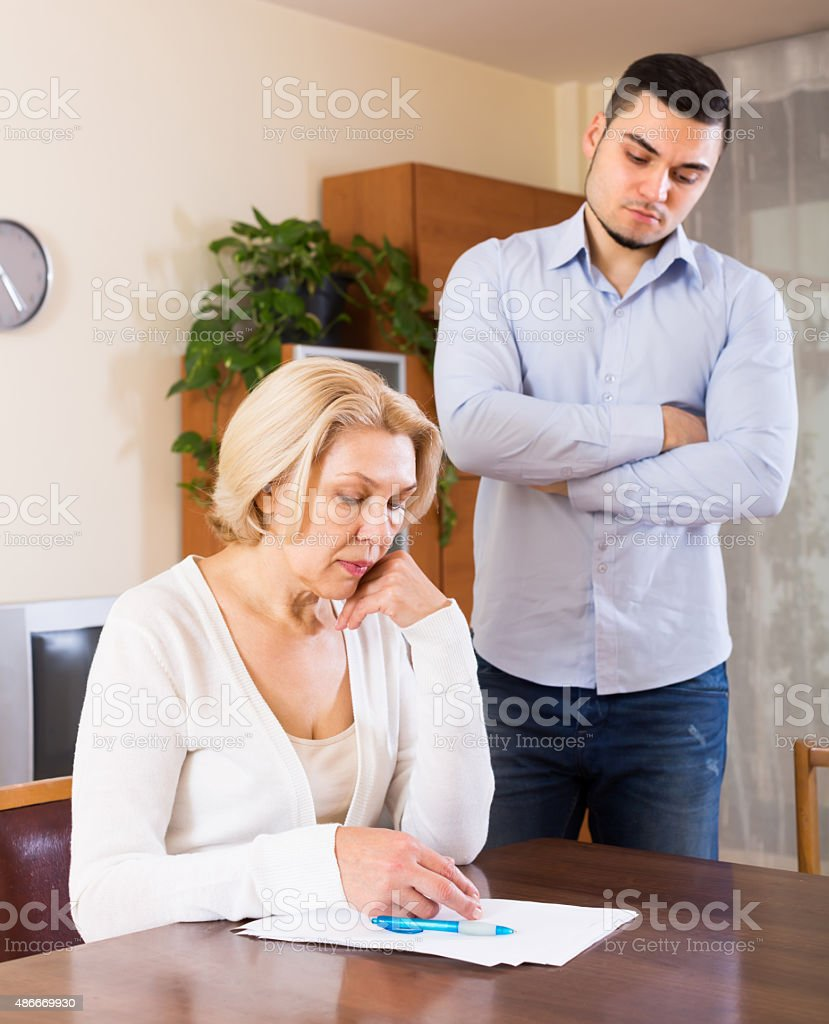 Elderly woman and young man with bills stock photo