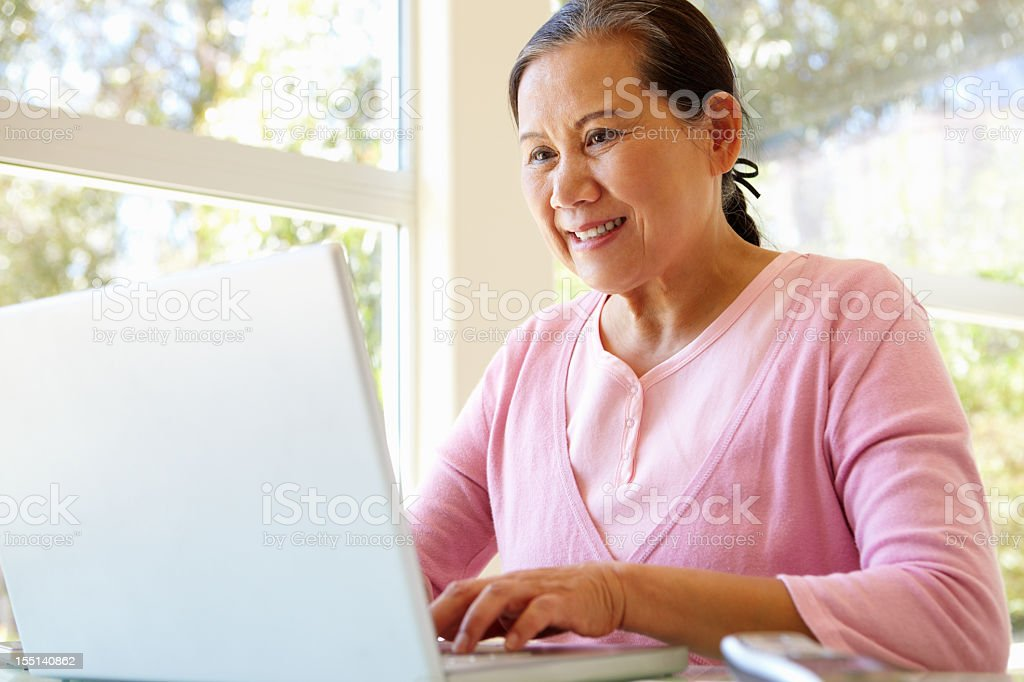 Elderly woman at home on her laptop stock photo