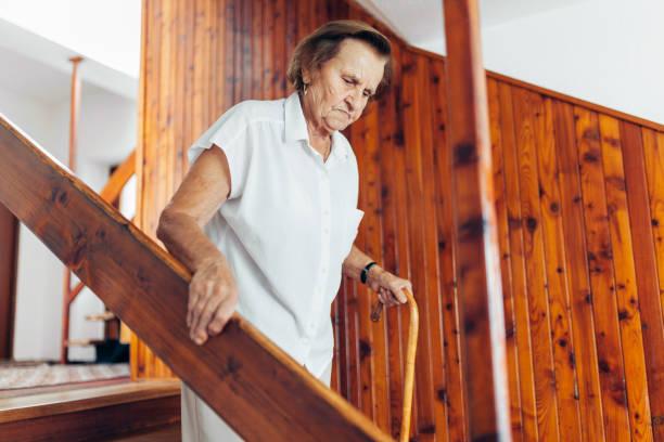 Ältere Frau zu Hause verwenden einen Stock, die Treppe hinunter zu bekommen – Foto