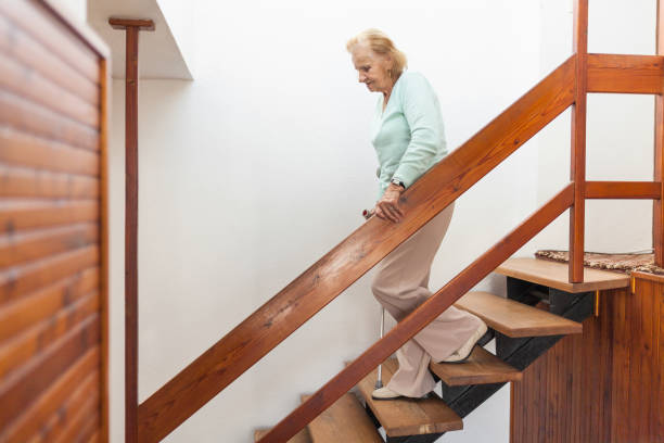 Ältere Frau zu Hause mit einem Stock, um die Treppe hinunter zu bekommen – Foto