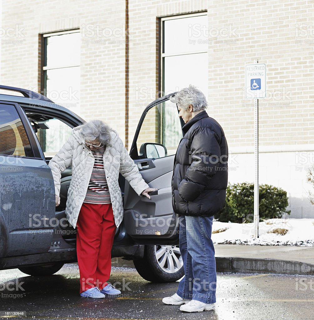 Elderly Woman Backing Into Car Front Seat royalty-free stock photo