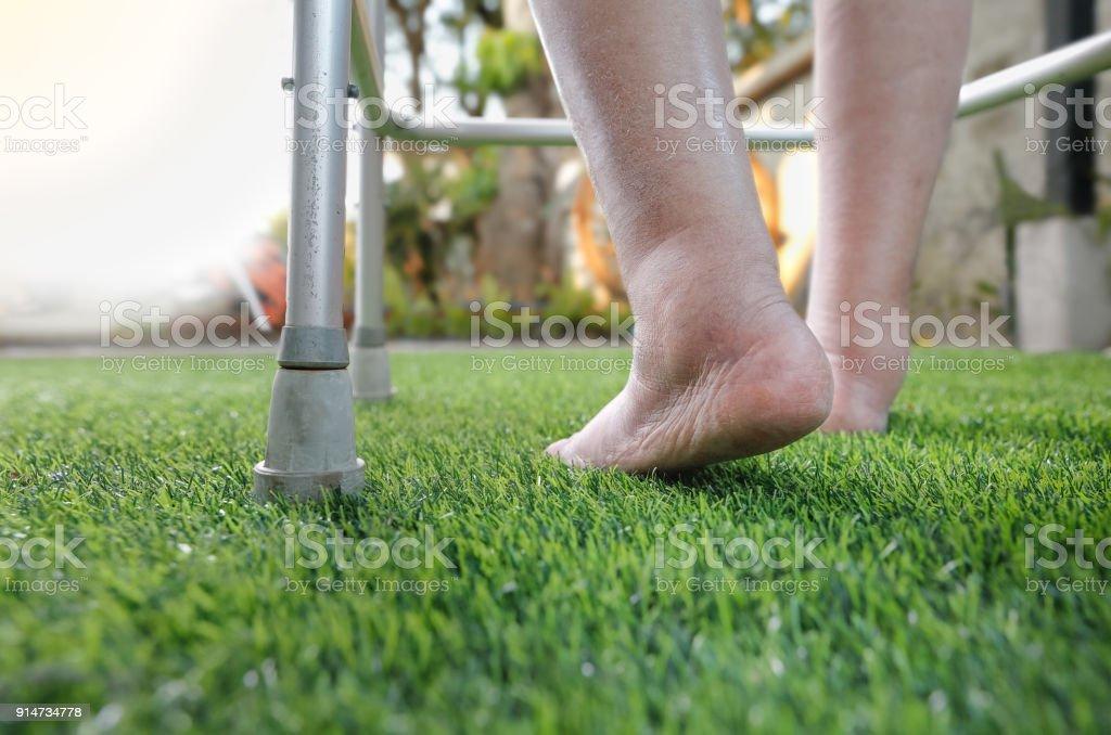 Ältere Frau kahl, geschwollene Füße auf dem Rasen mit walker – Foto