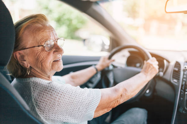 elderly woman behind the steering wheel - driver stock photos and pictures
