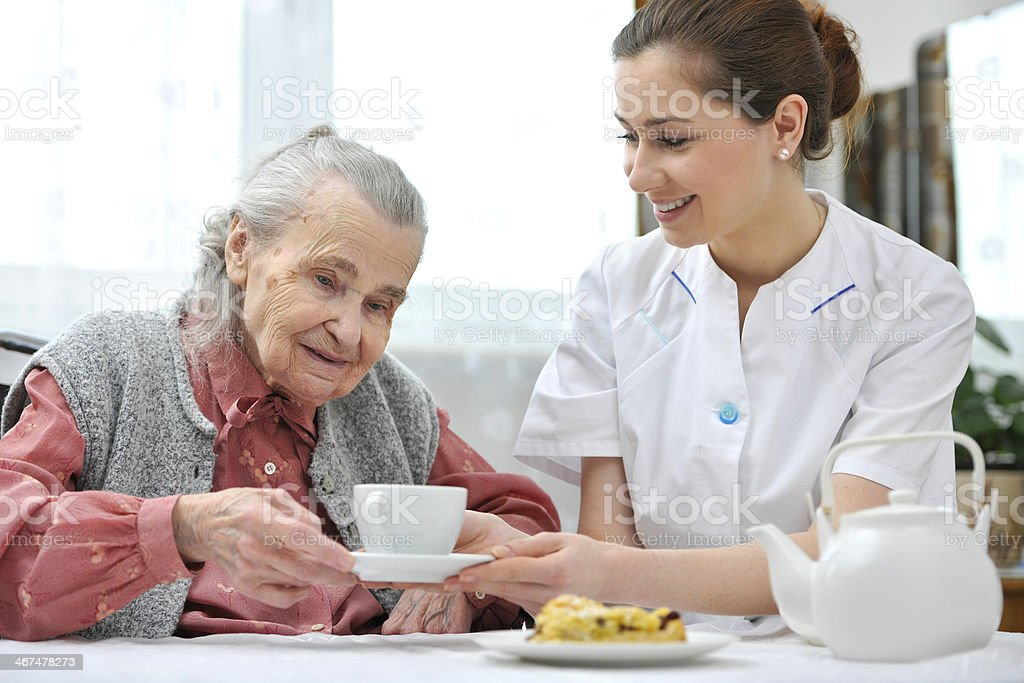 Elderly woman being served cup and saucer at nursing home royalty-free stock photo