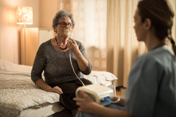 Elderly woman breathing through oxygen mask during home therapy. Senior woman having a visit from home caregiver and breathing through mask during medical oxygen therapy. oxygen mask stock pictures, royalty-free photos & images