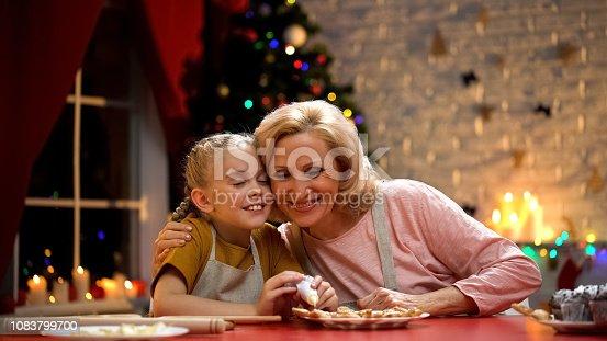 Elderly woman carefully hugging her little granddaughter, preparations for Xmas