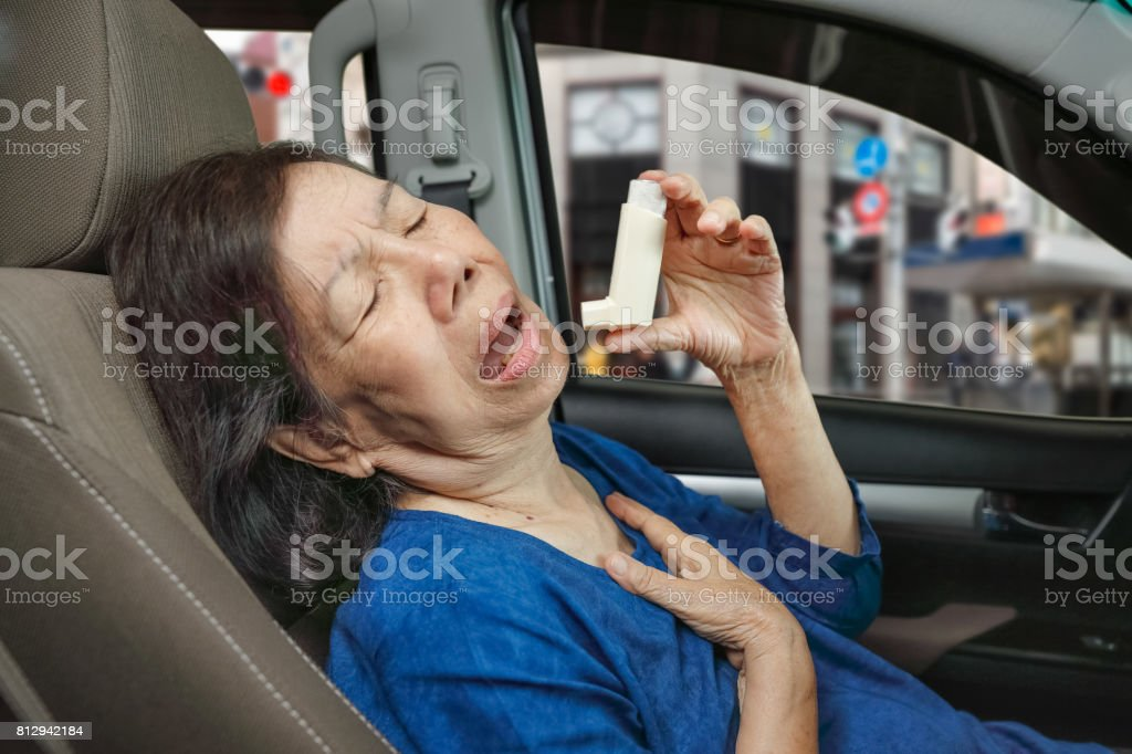 Elderly woman choking and holding an asthma spray inside car on the way stock photo
