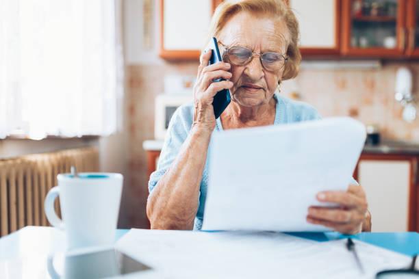 Ältere Frau, die Kontaktaufnahme mit Custumer Service nach Erhalt einer Rechnung – Foto