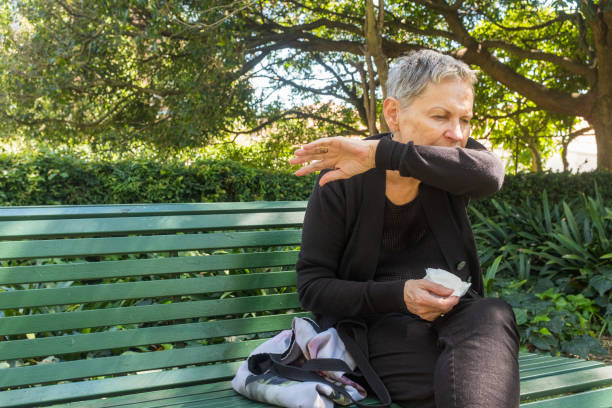 Elderly woman coughing into elbow and holding tissue outdoors stock photo