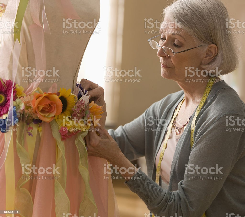 Elderly woman designing flowered skirt royalty-free stock photo