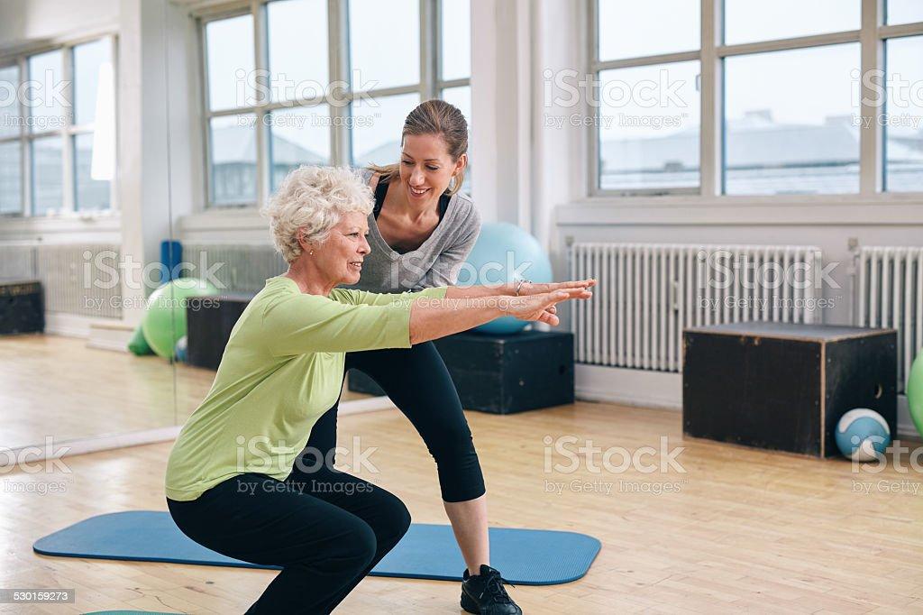 Idosos mulher fazendo exercícios com seu instrutor pessoal - foto de acervo