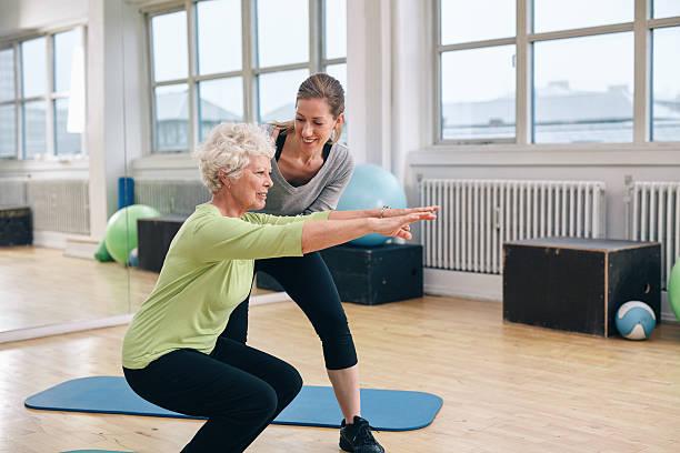 edad mujer haciendo ejercicios con su entrenador personal - agacharse fotografías e imágenes de stock
