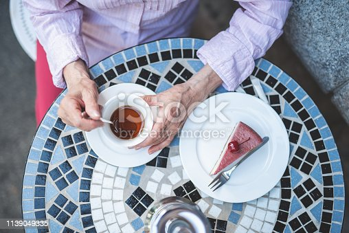 Top view of senior female hands holding cup of tea. Old lady is sitting at table and eating cake with berries