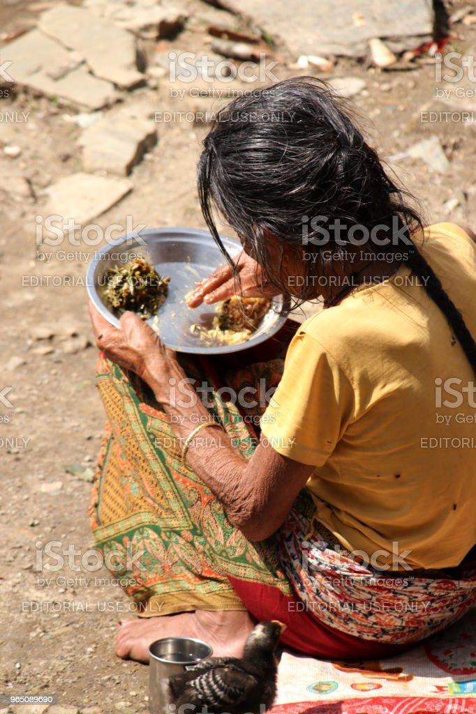 Elderly woman eats in front of her home, Nepal zbiór zdjęć royalty-free