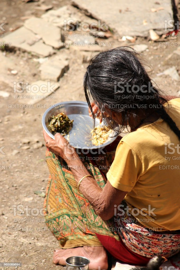 Elderly woman eats in front of her home, Nepal royalty-free stock photo