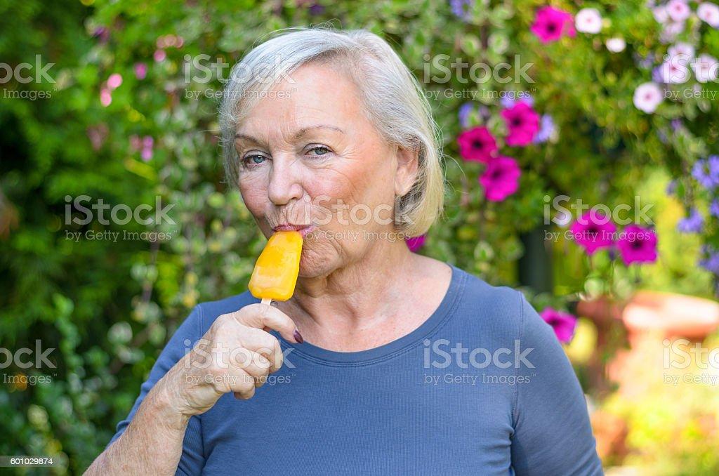 Elderly woman enjoying a refreshing iced lolly stock photo