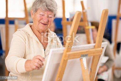 585509074 istock photo Elderly woman enjoying art department. 1125617803