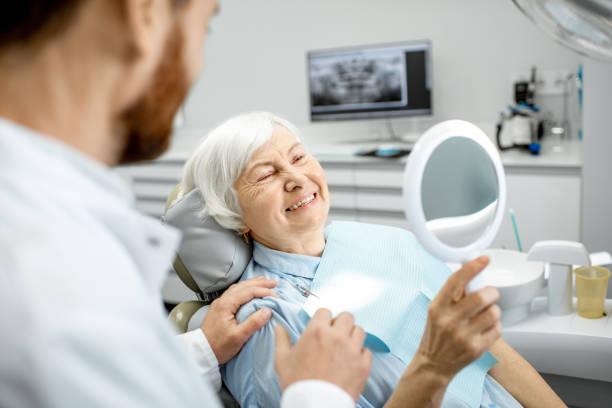 Elderly woman enjoying her smile in the dental office Happy elderly woman enjoying her beautiful toothy smile looking to the mirror in the dental office implant stock pictures, royalty-free photos & images