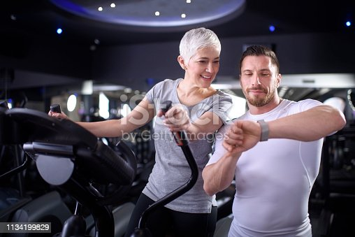 Active senior woman exercising on a cross trainer. Her personal coach is motivating her and showing her progress on a fitness tracker app on a smart watch.