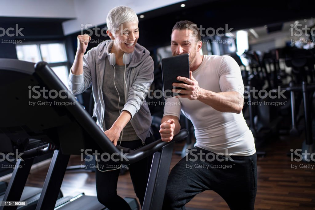 Elderly Woman Exercising On A Treadmill In A Gym Her Personal