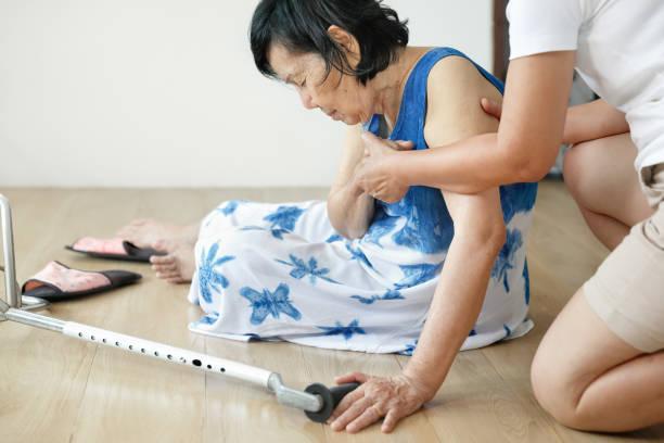 Ältere Frau fällt zu Hause nieder, Herd angreifen. – Foto