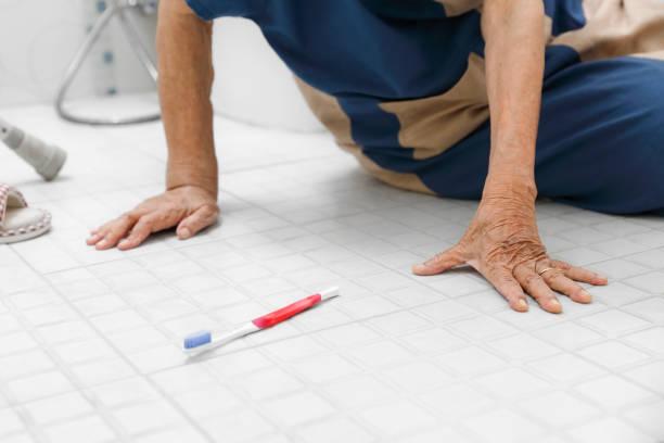 Ältere Frau fällt im Badezimmer, weil rutschige Oberflächen – Foto