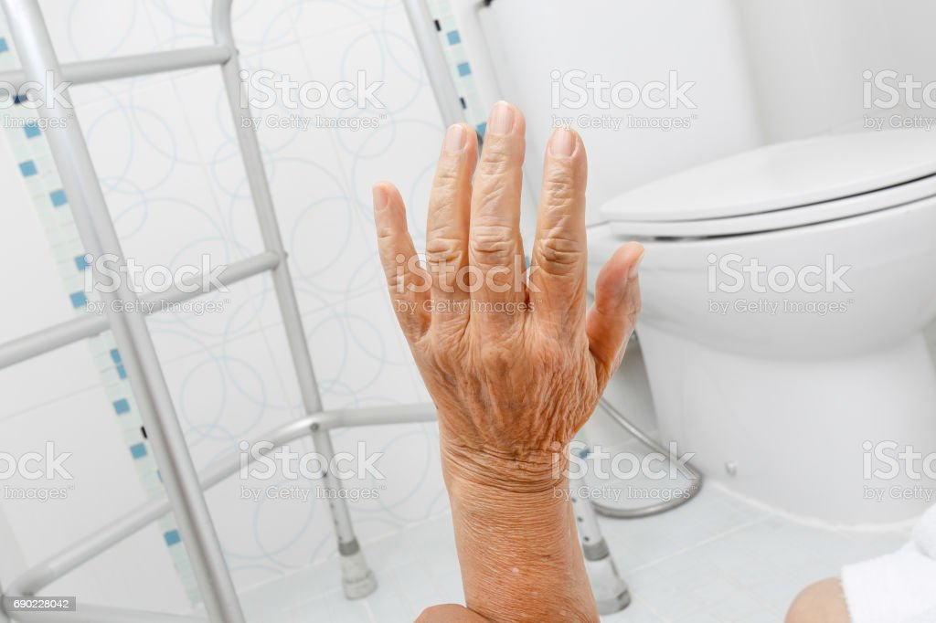 Elderly woman falling in bathroom because slippery surfaces stock photo