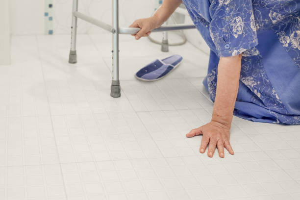 elderly woman falling in bathroom because slippery surfaces - fall prevention stock photos and pictures