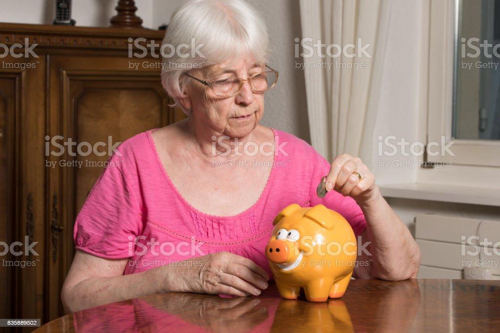 Elderly woman feeding her piggybank stock photo