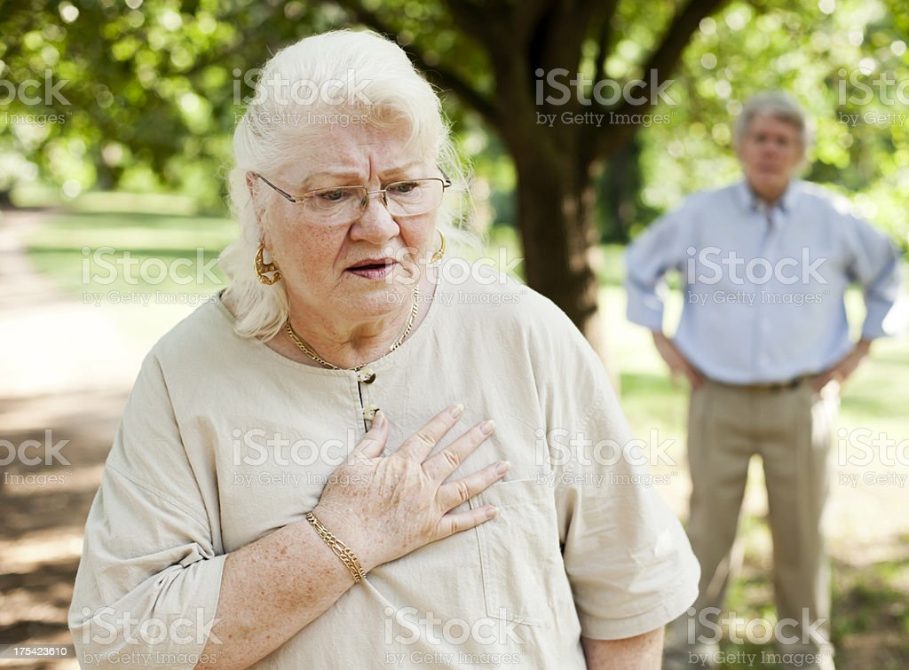 Elderly woman feeling pain in her chest stock photo