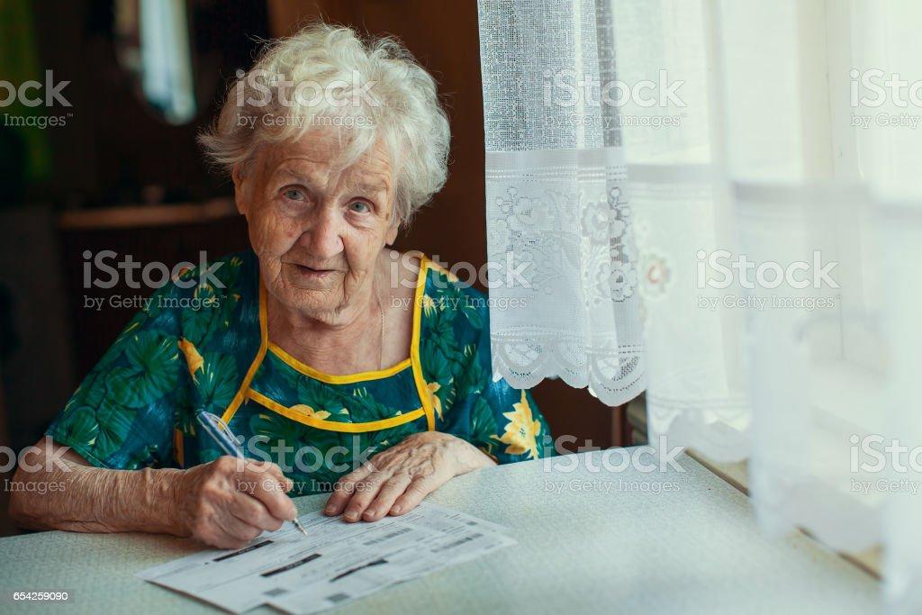 Ältere Frau füllt Stromrechnungen. – Foto