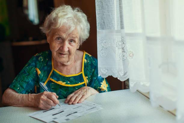Elderly woman fills out utility bills. stock photo