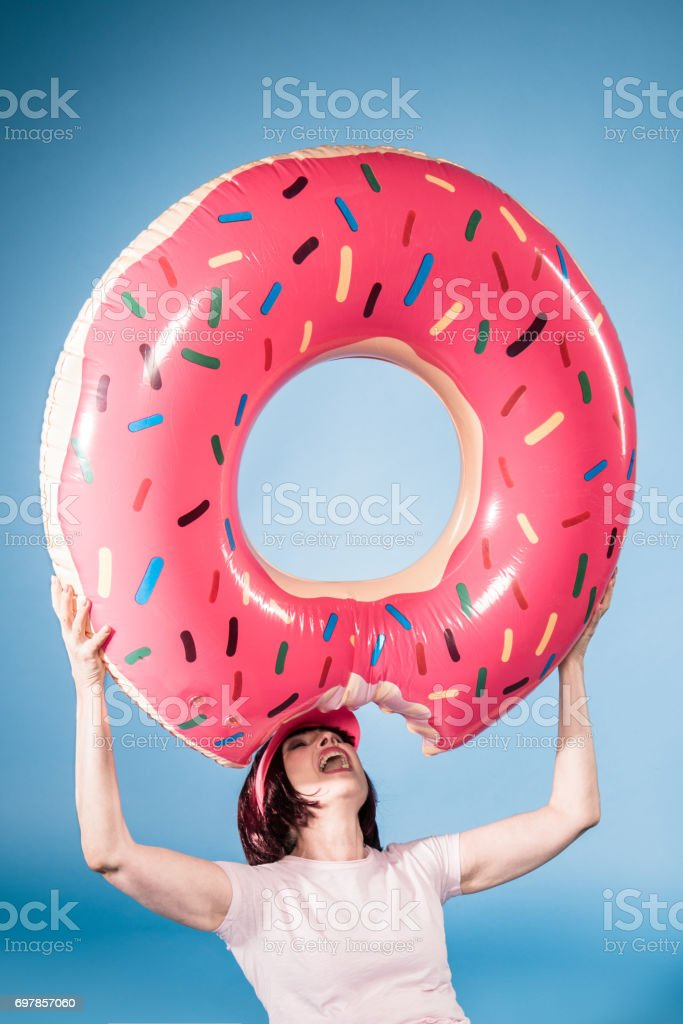 elderly woman fooling around with float ring in form of doughnut stock photo