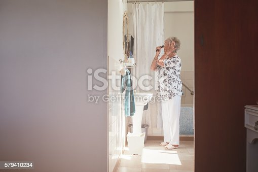 istock Elderly woman getting ready in bathroom 579410234