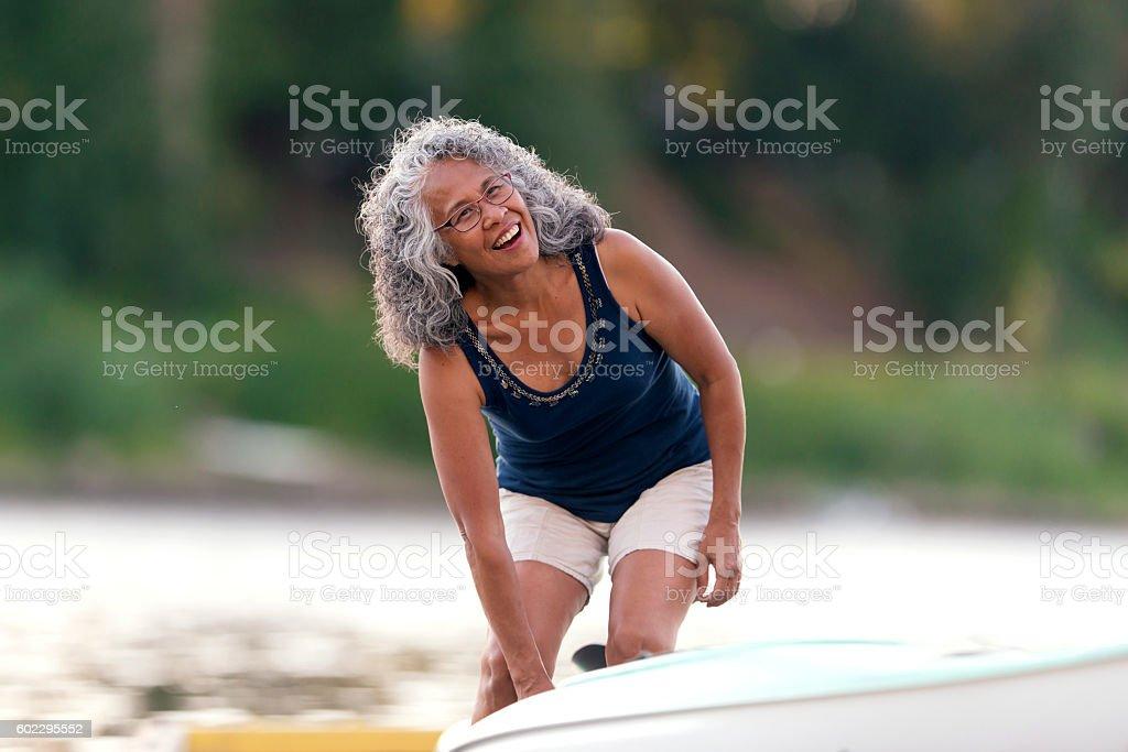 Elderly woman getting ready to kayak stock photo