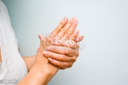 istock Elderly woman grasping arthritic hands 183841607