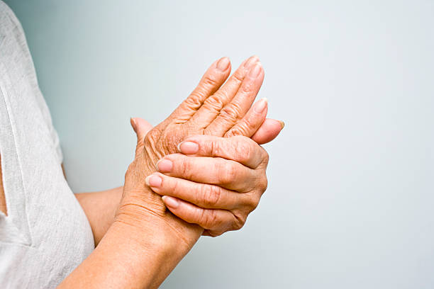 Elderly woman grasping arthritic hands stock photo