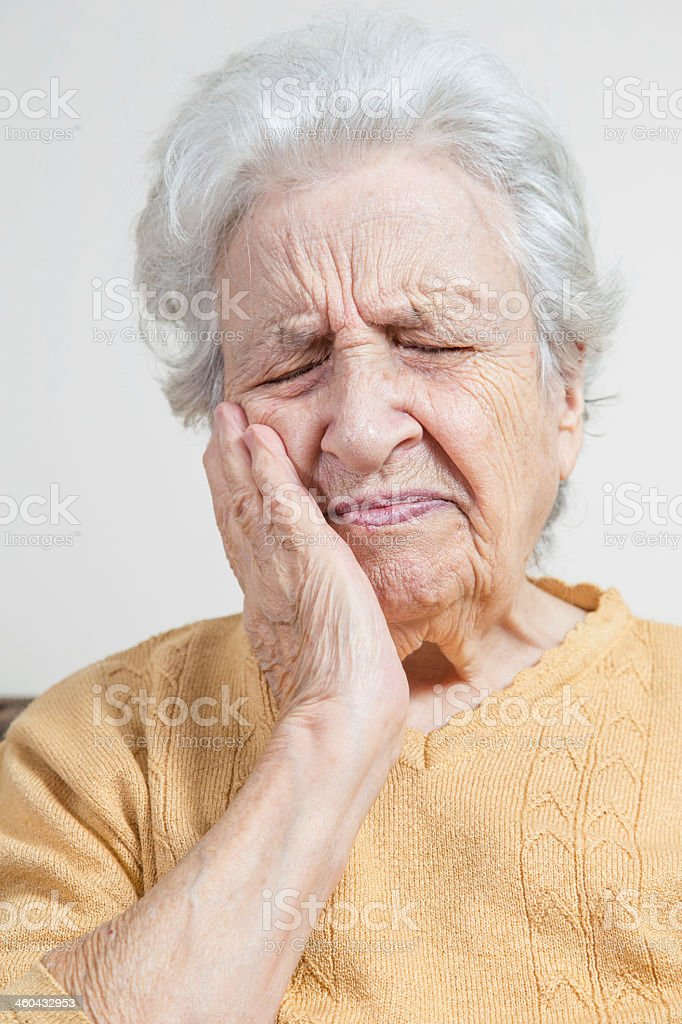 Elderly woman grasping cheek and wincing in pain stock photo