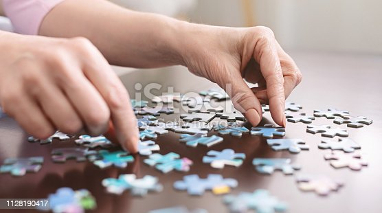 istock Elderly woman hands doing jigsaw puzzle closeup 1128190417