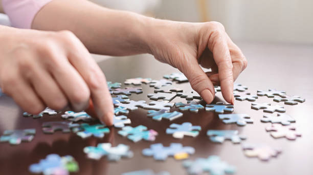Elderly woman hands doing jigsaw puzzle closeup Dementia prevention. Elderly woman hands doing jigsaw puzzle at home, panorama, close up hobbies stock pictures, royalty-free photos & images