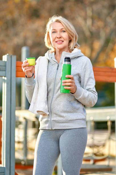 Una anciana tomando una copa después de hacer deportes al aire libre. - foto de stock