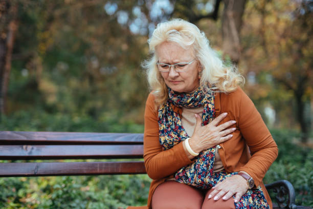 Elderly woman having chest pains or heart attack in the park stock photo