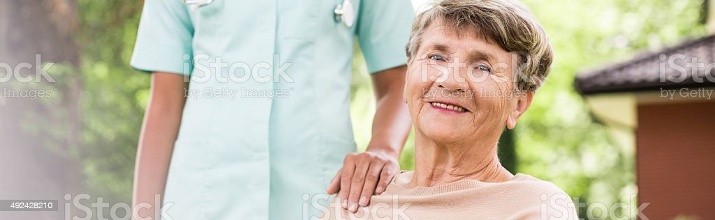 Elderly woman having private medical care stock photo