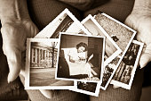 Toned image of an elderly, senior woman holding old vintage photographs of herself and of other places in her hands, showing her sentimental memories, past, and places travelled.  Only her hands are shown in the image